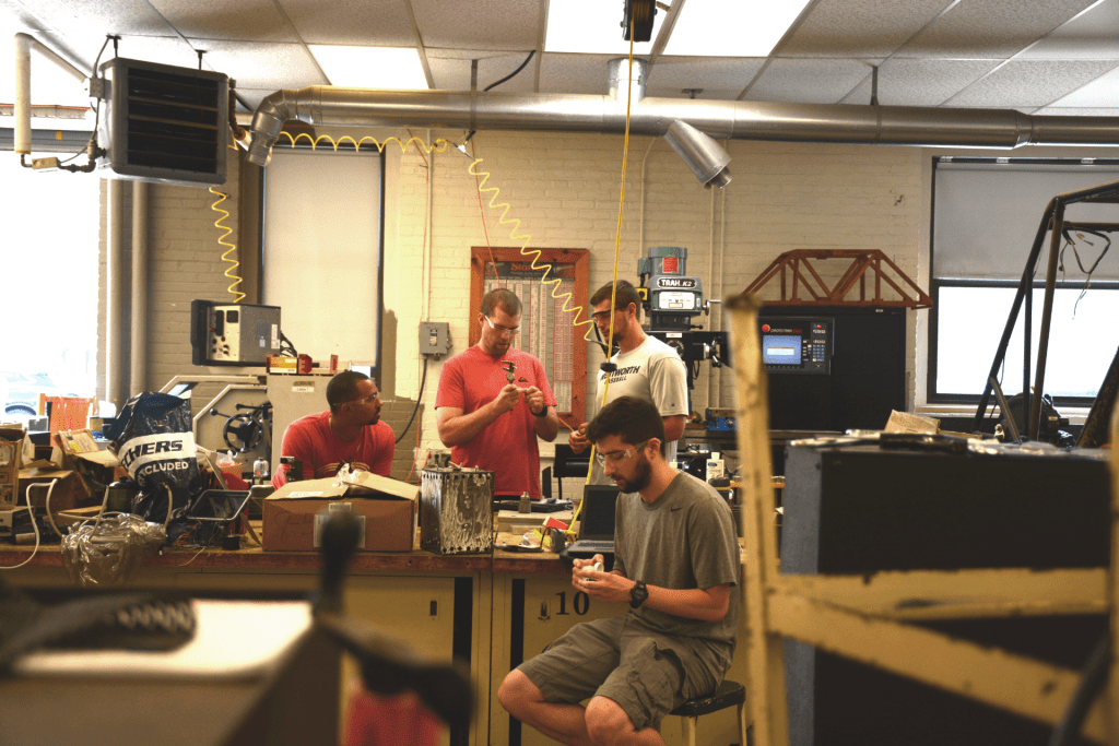 four men working in a projects lab