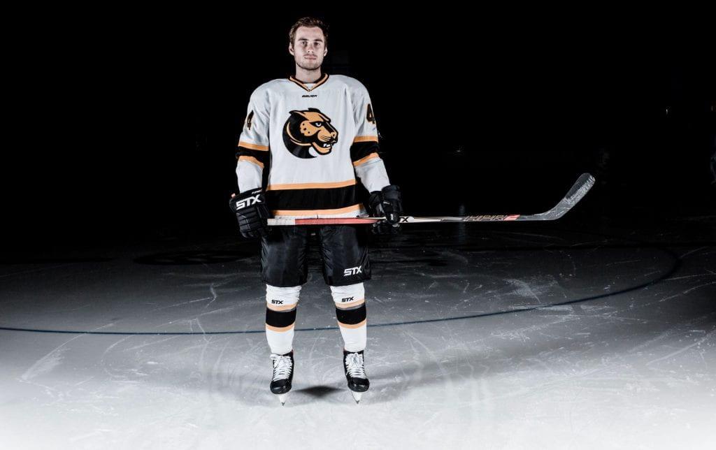 man in hockey uniform standing on ice