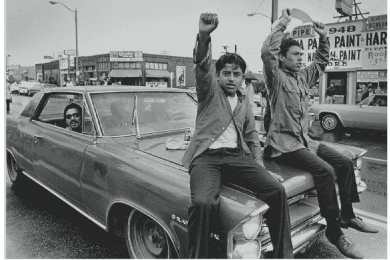 Two young Chicano men ride on the hood of a car during a national Chicano Moratorium Committee march in opposition to the war in Vietnam.