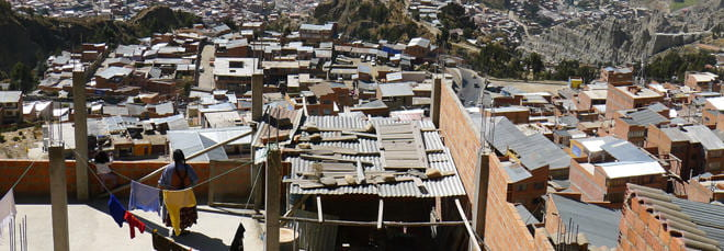 Photo of the dense housing in La Paz. A woman on her rooftop hangs laundry on a line to dry.