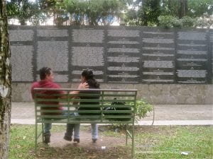 A couple sit on a bench across from a memorial wall.