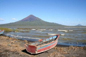 A small abandoned red boat rests on the shoreline of Lake Managua in Nicaragua. In the background is a mountain.