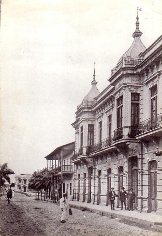 Historic photo of a museum, with dirt lined roads and a horse in the street.