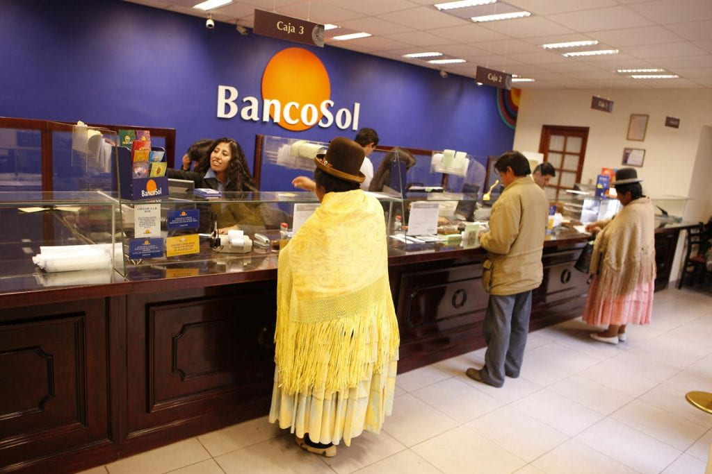 Photo of interior of the El Alto branch of BancoSol, with cuistomers in traditional and indigenous attire transacting bank business with tellers.