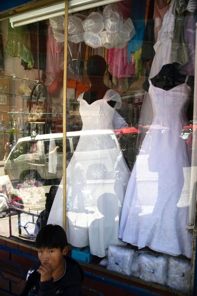 Photo of a young man sitting on a bench in front of a bridal shop, with two wedding dresses in the window display.