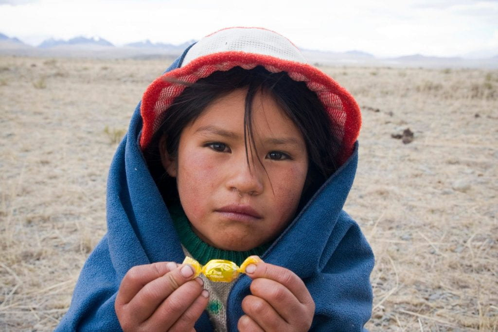 An indigenous child holding a prized piece of candy.