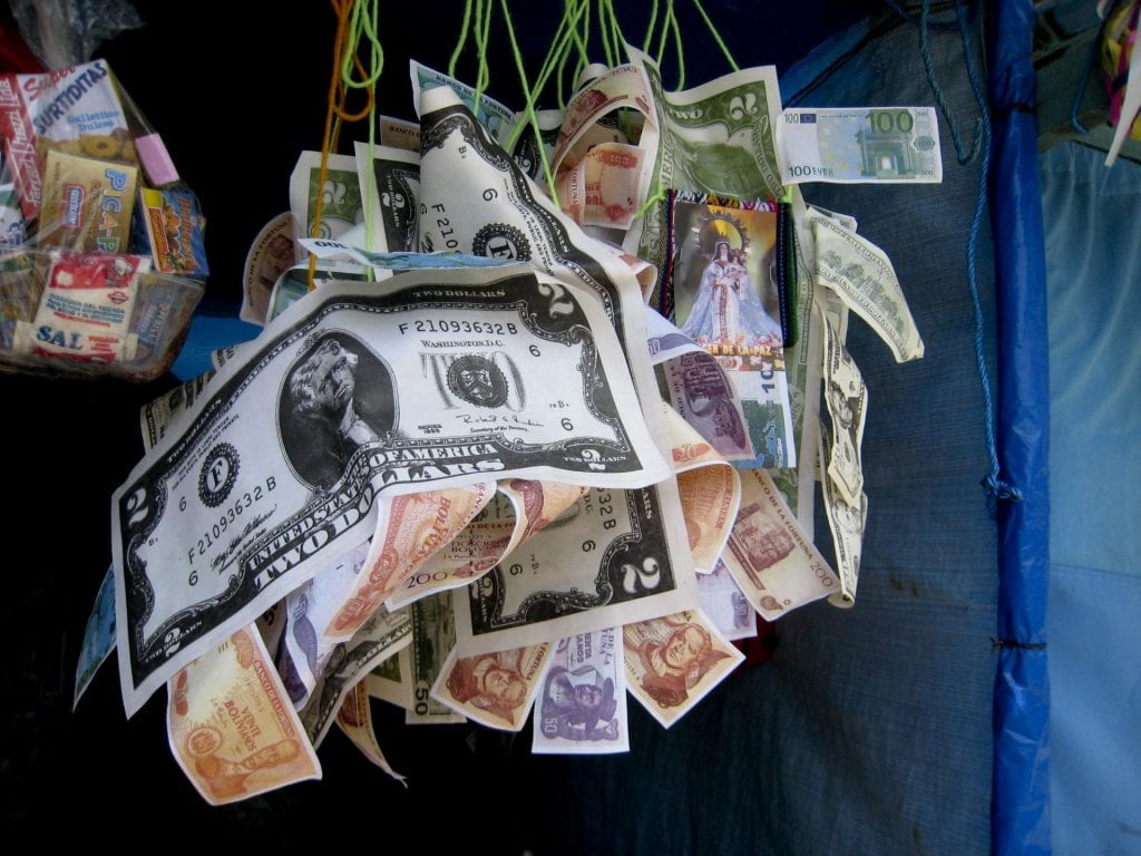 Miniature dollar bills mingle with Bolivianos in the traditional Bolivian alasitas festival.