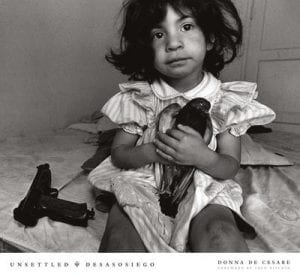 Cover of book, Unsettled/Desasosiego, Children in a World of Gangs, by Donna DeCesare. The cover photo shows a young girl sitting on a bed with a bird in her hand and a handgun next to her.