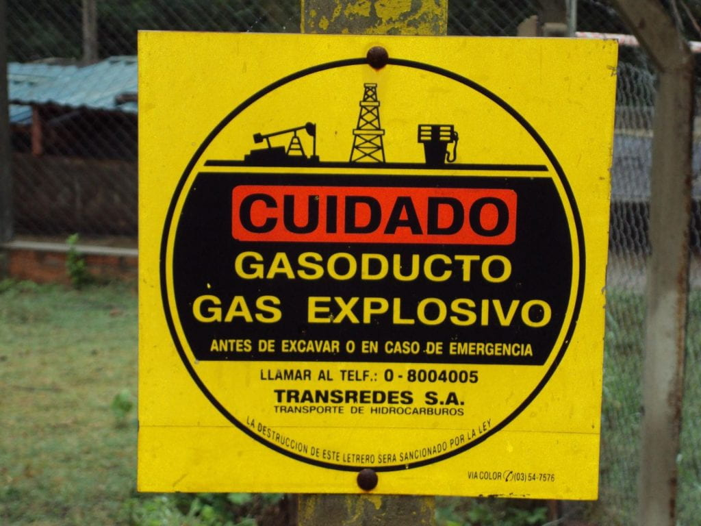 A yellow warning sign, with the words WARNING in red, warning of ex[plosive gases.