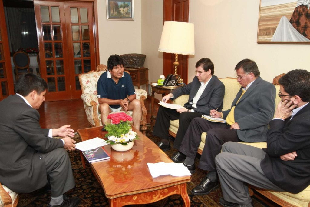 Photo of President Evo Morales interviewed by four reporters in his home. They are seated around a coffee table.