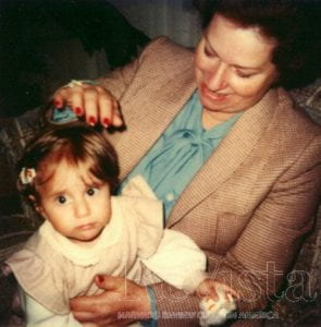 Phot of the article's author Laura Barragán Montaña as a young child in the lap of her grandmother. Photo courtesy of Laura Barragán Montaña