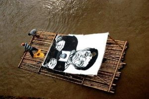 Photo of the artist Gabriel Posada, on a raft in the Cauca River with Vinyl paint images of the disappeared in