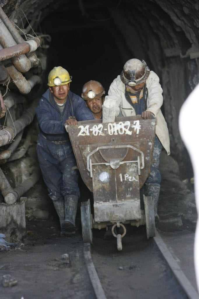 A photo of three miners pushing a railcart out of a mine.