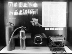 Display from the new Museum for Independence, which honors victims of the conflict in its hot spot project. The display shows photos of victims, a list of victims, and artifacts that symbolize their lives--a typewriter, a fire extinguisher, a helmet.