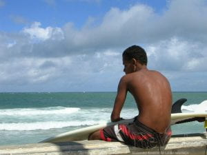 A young man with a surfboard gazes out at the water in Salvdor da Bahia, in northeastern Brazil.