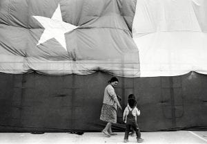 A woman and two young children walk before an enormous Chilean flag.