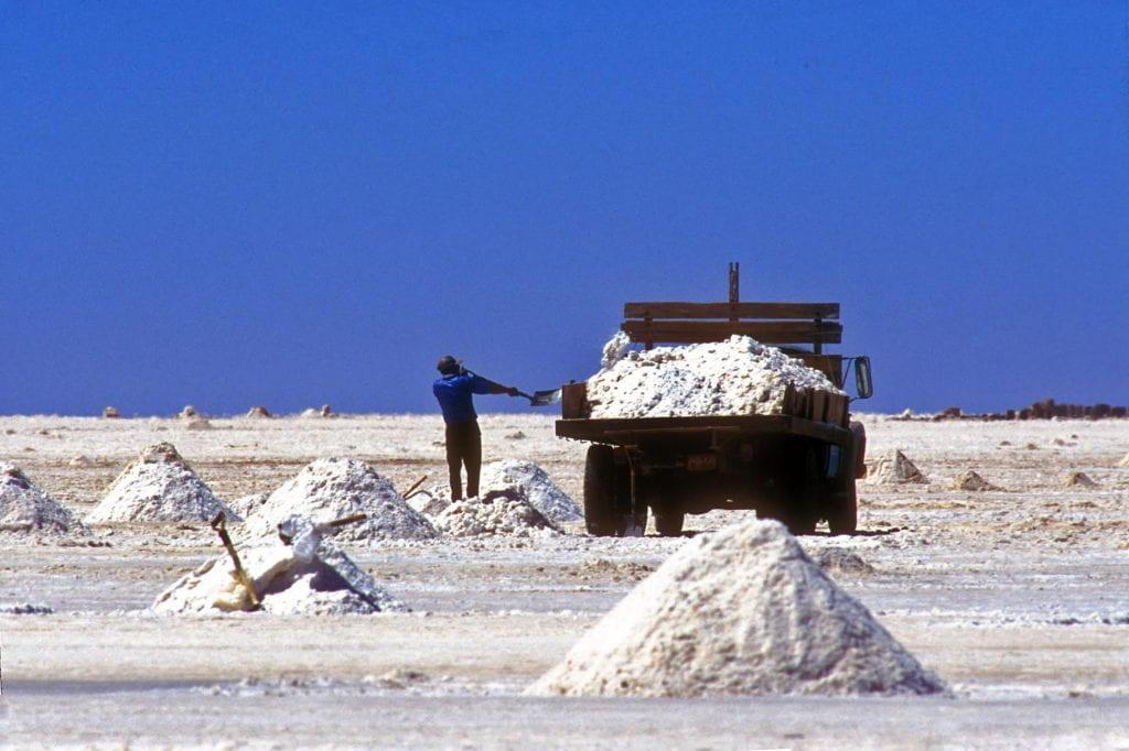 Photo of a salt mine in Salar de Uyuni, showing piles of salt, as well as a man shoveling salt into a truck.