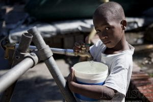 A child collects water from a bladder in a camp near the slum of Cité de Dieu, in Port-au-Prince.