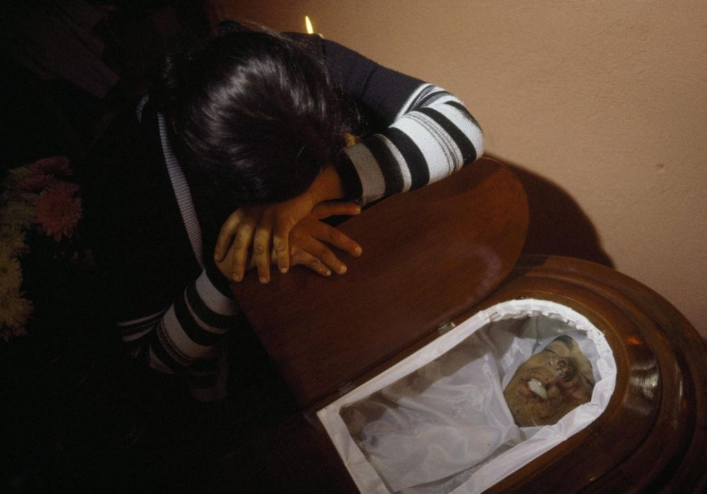 A woman cries at the casket during the wake for Hector Gomez Calito, founding member of Mutual Support Group for the Families of the Disappeared (GAM), Amatitlán, 1985.