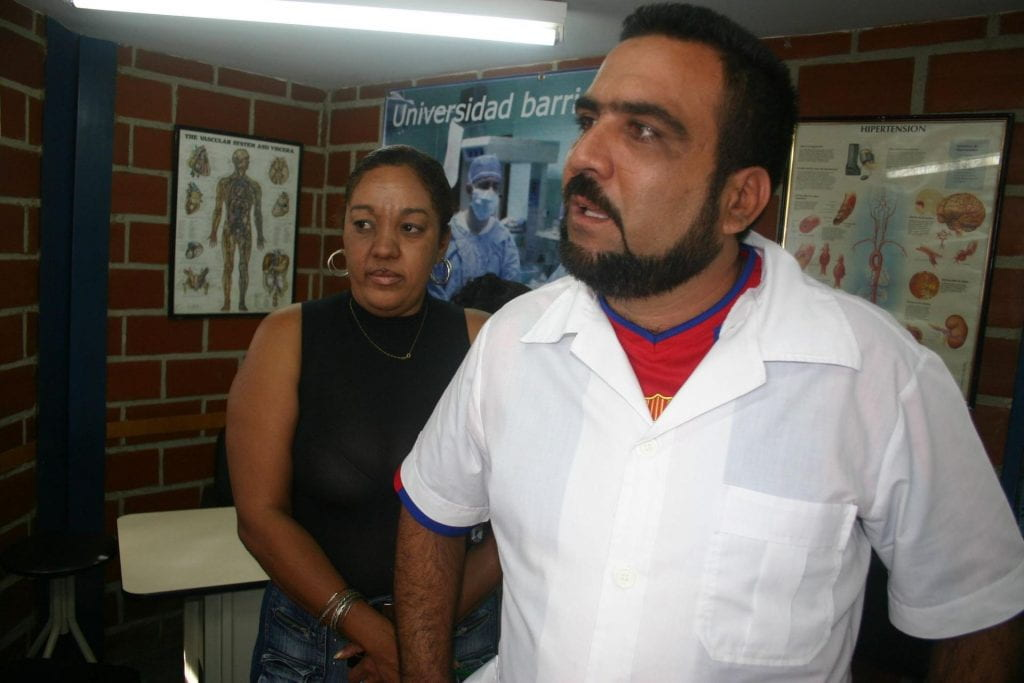 A male Cuban doctor with beard, wearing a white short-sleeve shirt and red undershirt, stands in a brick office, which has several medical posters on the wall.