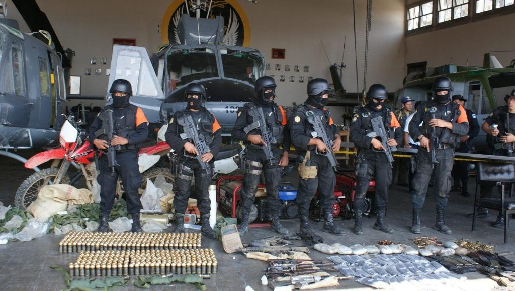 A photo showing an arsenal of weapons and drugs seized during a raid. Behind the weapons and drugs stand six police with machine guns.