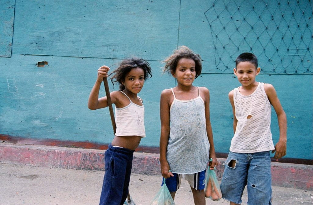 Three school-age children pose for a picture. One of them is carry plastic bags of vegetables.
