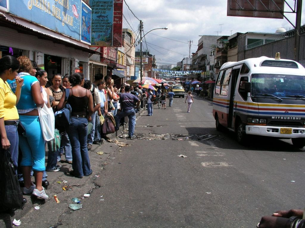 On a city street, people wait in a long line. Lines for buses and food supplies are a common sight.
