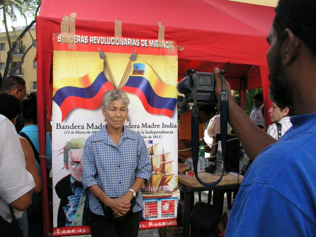 A woman in a blue shirt gets her photograph taken for her Bolivarian ID card for subsidies.
