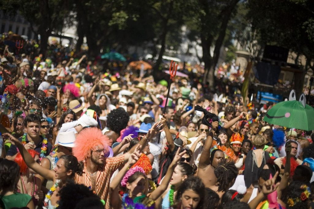 A crowded street in Rio de Janeiro for the Carnaval. People are wearing colorful necklaces and wigs.