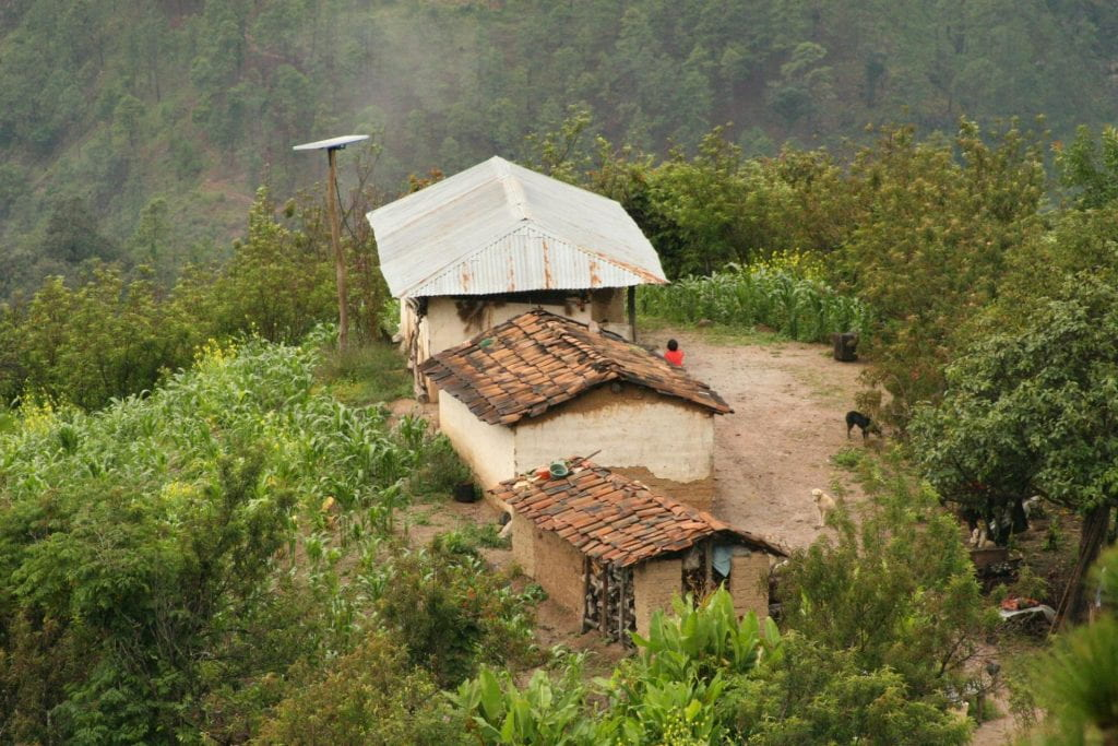 Cluster of mud huts with solar panels.
