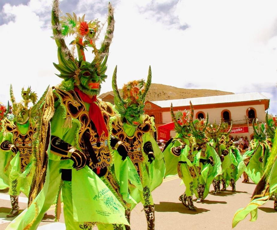 Images of the dancing devils, diablos dan- zantes, in Puno, Peru. A large group of dancers, with lime green and black costumes, and very long horns on their heads, represent the devils in the dance.