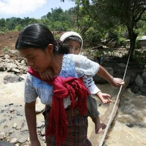 Photo of a mother carrying a child on her back, crossing a stream by walking over a tree trucnk. A rope has been attached to a tree to guide her.