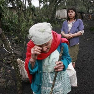 Photo of an elderly woman crying after a storm has left her property covered in mud.