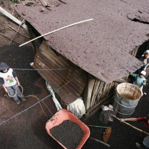 Photo of a family next to thjeir home, with two young boys clearing the mud from a storm.
