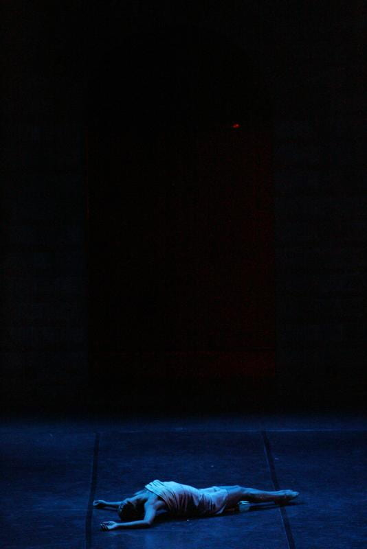 At the center of a large stage, with a black background and dimly lit blue light as highlights, a woman dancer lies on her back on the stage. Her arms extend back, depicting the impact of violence in El Otro Apóstol.