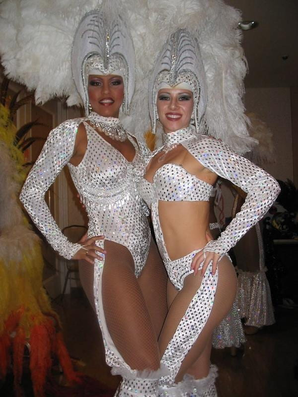 Two Brazilian passista dancers pose in their beaded thong and exaggerated headpiece. The article's author is on the right.