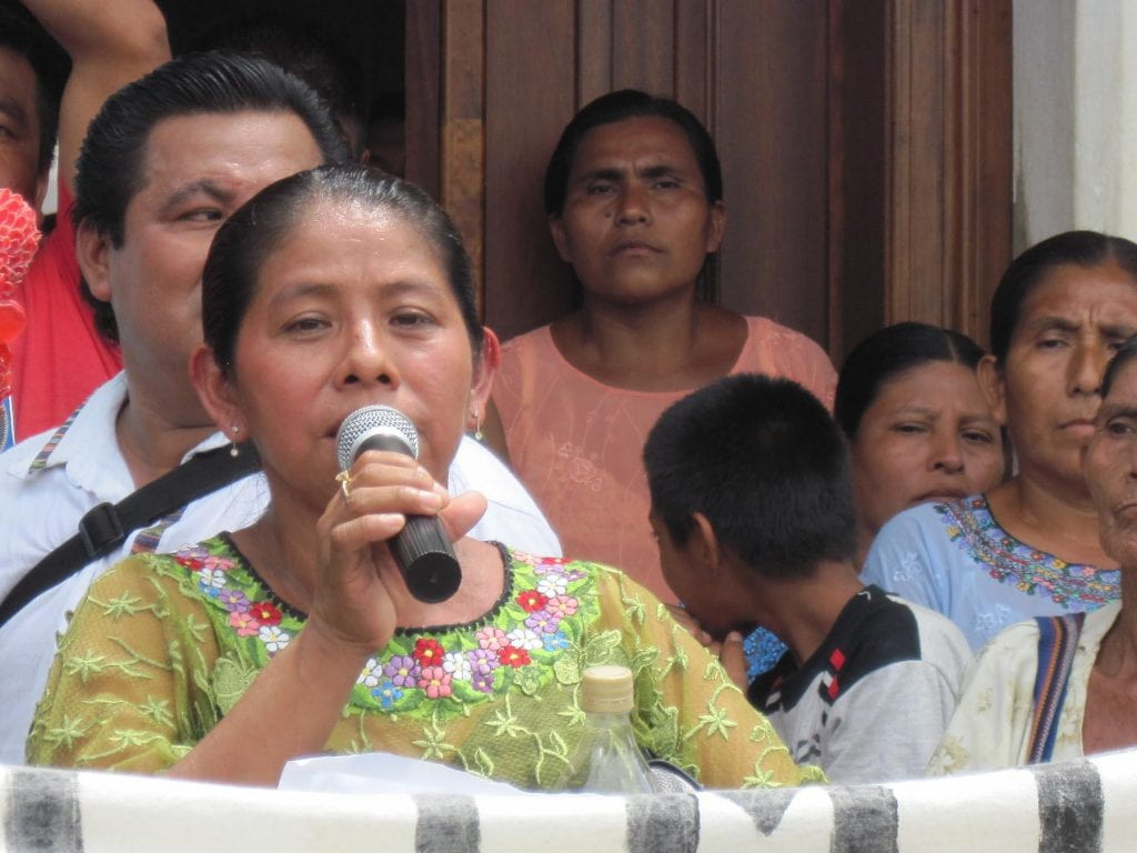 María Maquín, with microphone in hand, speaks out against the military base at a rally, surrounded by people.