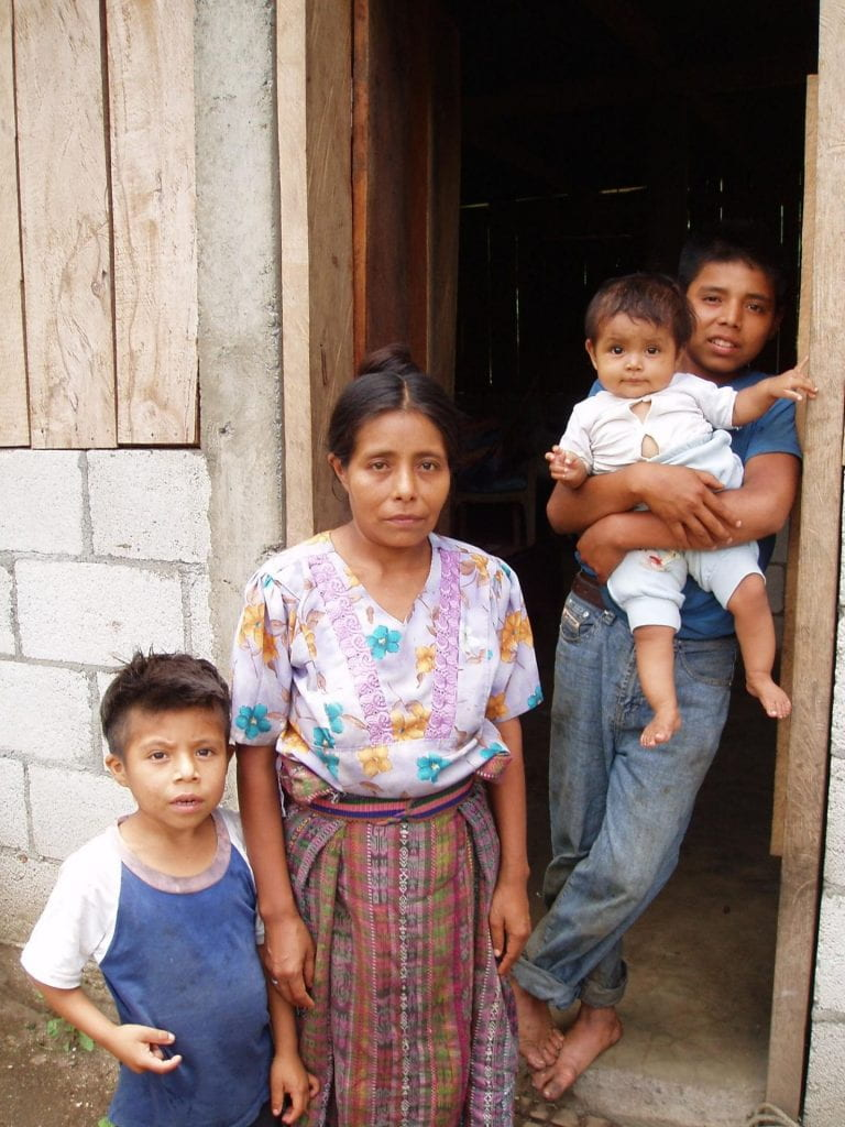 A local family (mother and three children) poses in their doorway