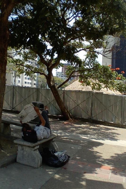 A young man, lying on a bench under the shade of a tree, reads the newspaper in a Caracas park.