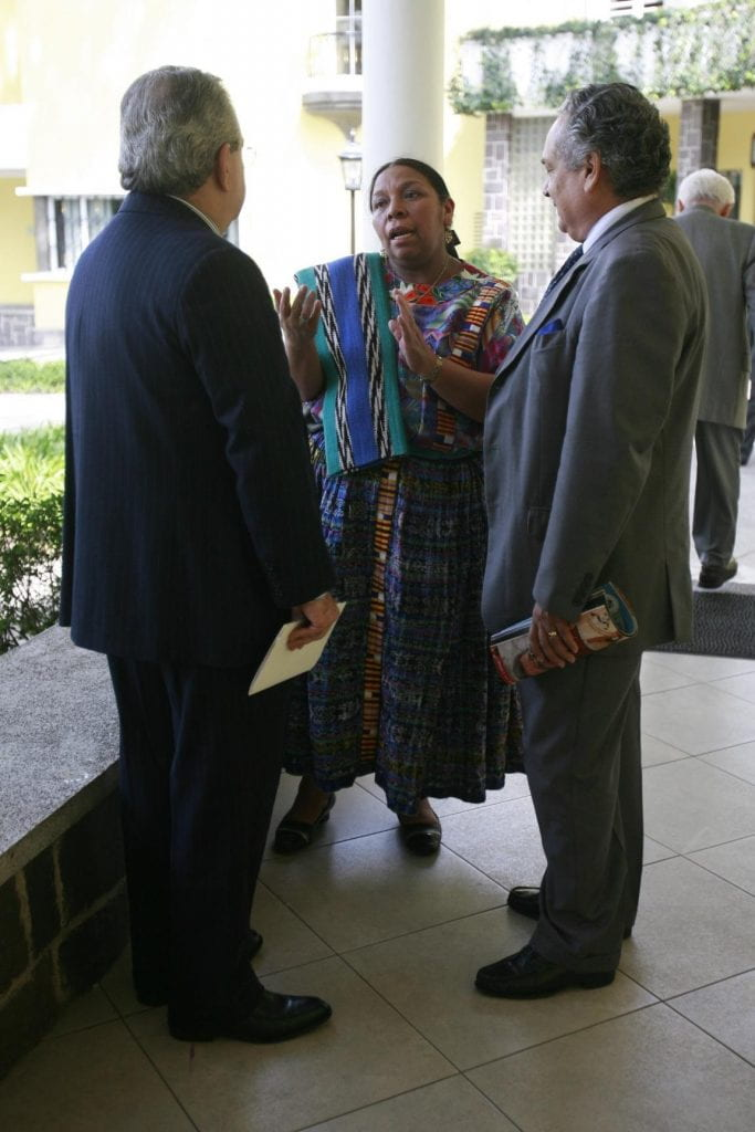 A professional Mayan woman wearing professional indigenous clothing engages in a conversation with two men in western business suits.