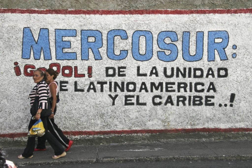 People walk past a wall mural praising Mercosur, a Common Market of the South.