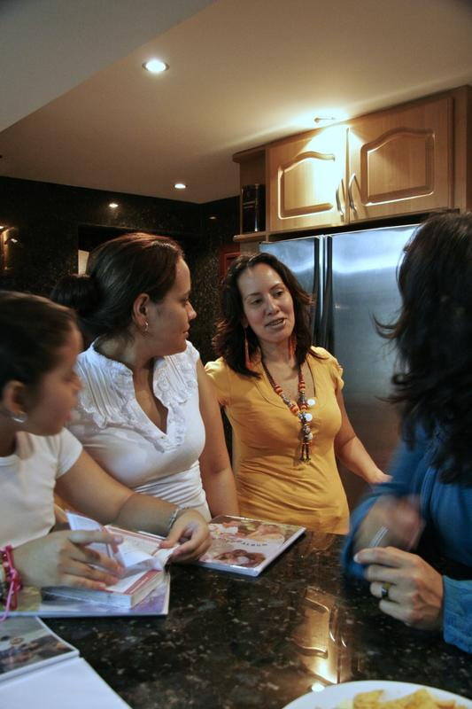 A Venezuelan woman teacher chats with young women in her kitchen.