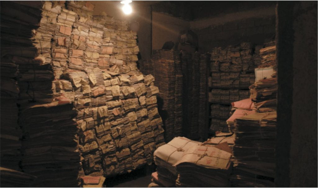 Bundles of documents are stacked to the ceiling at a police station archive in Guatemala City.