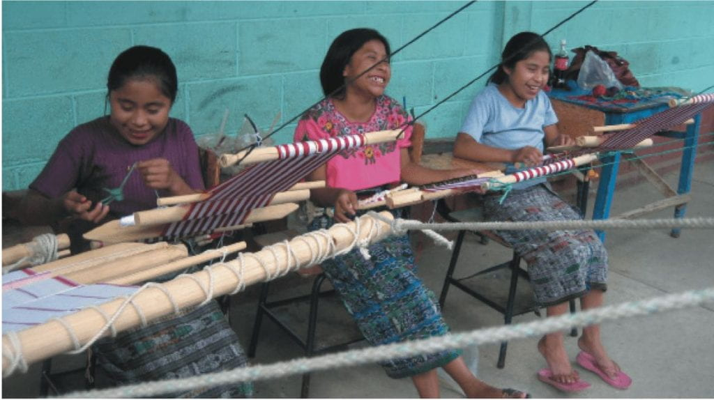 Photo of three indigenous girls at weaving tables.