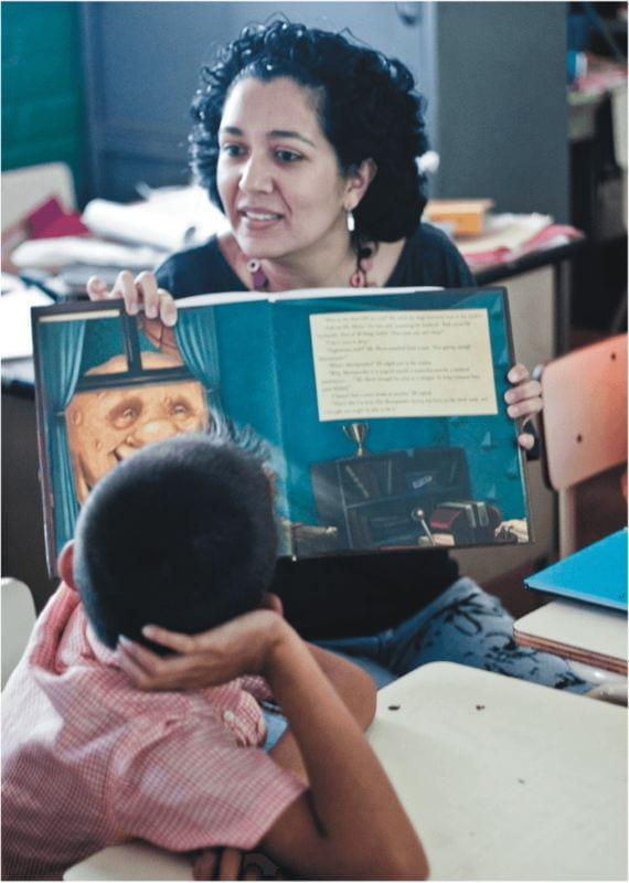 Photo of a teacher reading a picture book to children.