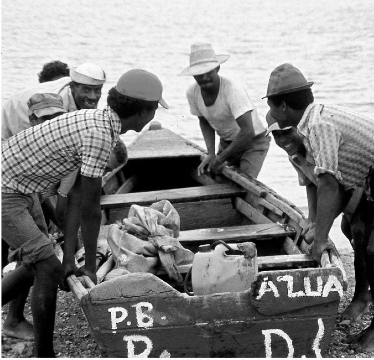Five men in short-sleeve shirts, shorts, and hats launch a small dory boat in the Dominican Republic.