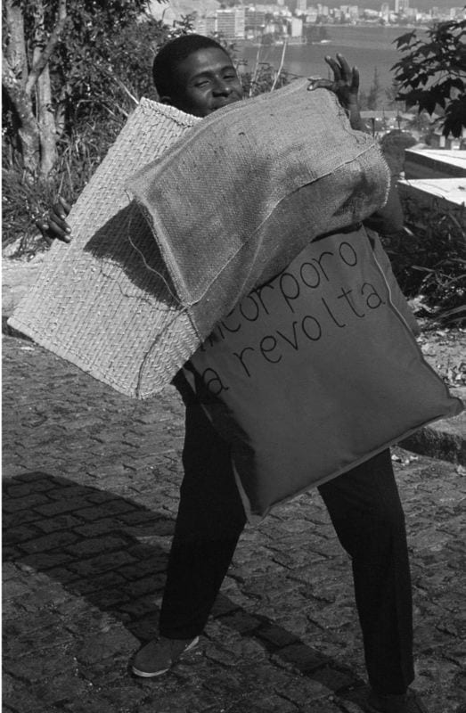 Photo of Nildo da Mangueira, wearing a Parangolé (protest sign) with the inscription read: Incorporo a Revolta (I Incorporate Revolt), which could be revolt against the lack of social mobility or against the authoritarian rule imposed by the military dictatorship. It implied a state of aggression as well as a wish for transgression.