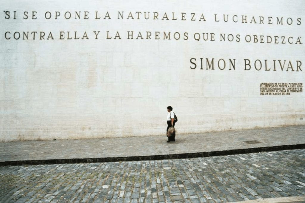 """A person walks by a large stone wall, with the letters displaying a slogan by Simón Bolívar, which translates to """"If nature opposes us, we'll fight against it and make it obey us."""""""