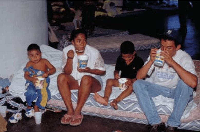 A family of four--parents and two children--sitting on a mattress on the floor of a shelter. There are other mattresses on the floor in the background. Te family eats food out of plastic containers.