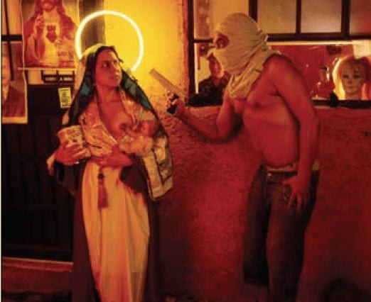 Photographer Nelson Garrido combines the sacred in profane in his photography. Here, the image depicts The Virgibn, with a neon halo heind her head and one breast exposed, being robbed by a man in a hood with a gun. Behind her to the left, there is a picture of Jesus.